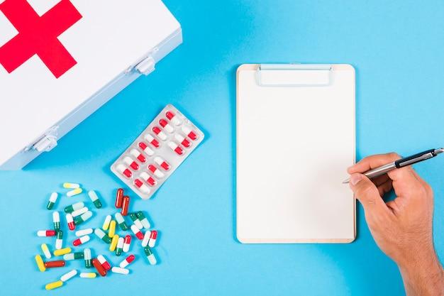 Een persoon die voorschrift op klembord schrijft met eerste hulpuitrusting en capsules op blauwe achtergrond Gratis Foto