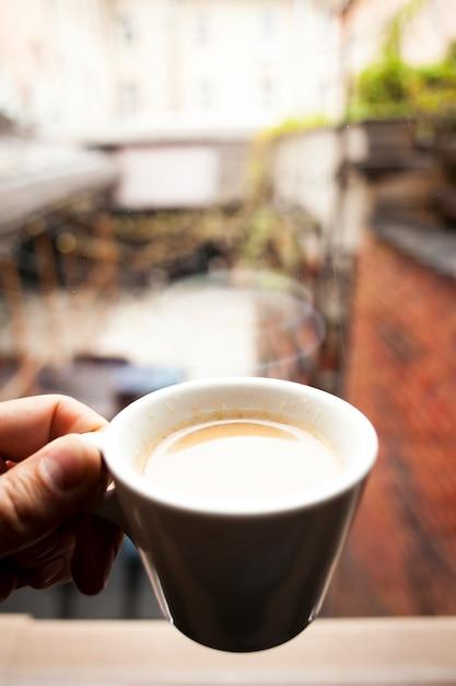Een persoon hand houden kopje koffie nadenken over vensterglas Gratis Foto