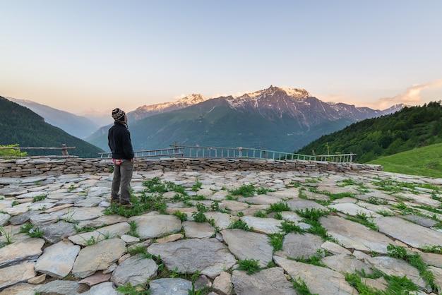 Eén persoon kijkt hoog in de alpen naar de zonsopgang Premium Foto