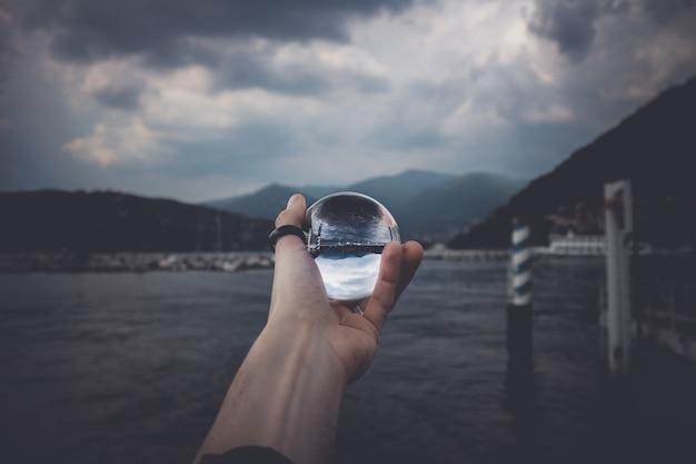 Een persoon met een kristallen bol met de weerspiegeling van hoge bergen en prachtige wolken Gratis Foto