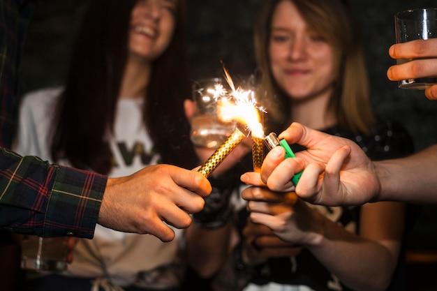 Een persoon verlichting sprankelt kaars met aansteker met vrienden Gratis Foto