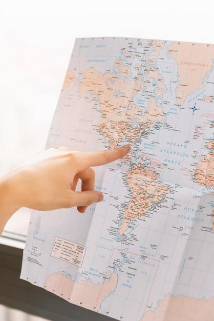 Een persoon wijzende vinger naar de locatie op de kaart Gratis Foto