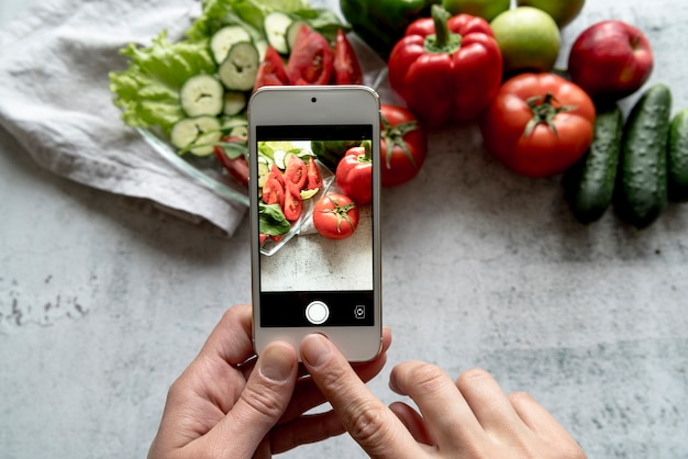 Een persoonshand die beeld van verse groente op achtergrond neemt Gratis Foto