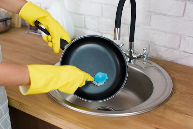 Een persoonshand met de gele pan van de handschoenwas met borstel in keuken Gratis Foto