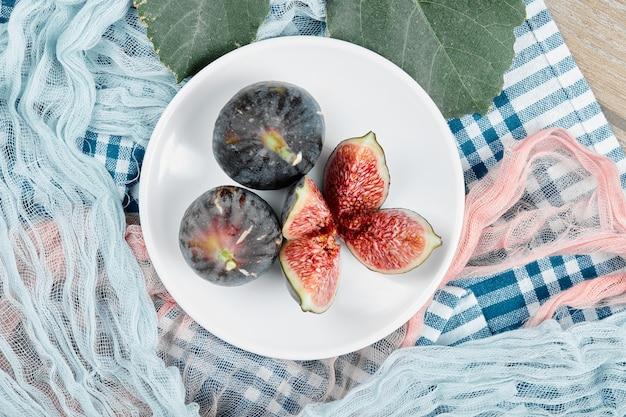 Een plaat van hele en gesneden zwarte vijgen, een blad en blauwe en roze tafelkleden op houten tafel. Gratis Foto