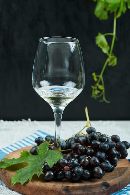 Een plaat van zwarte druiven met blad en een glas wijn op donkere ondergrond Gratis Foto