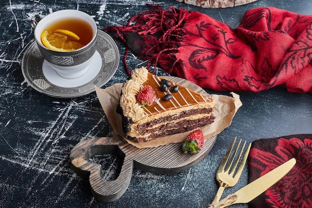 Een plakje chocoladekaramelcake met een kopje thee. Gratis Foto