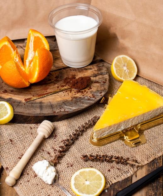 Een plakje citroen, sinaasappelroomkaastaart met melk. Gratis Foto