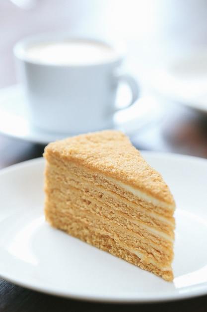 Een plakje honing cake met een kopje melk Gratis Foto
