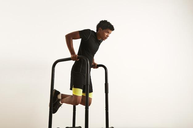 Een portret van een gefocuste gespierde afro-amerikaanse jonge man in zwarte training kleren dips op parallelle staven op wit Gratis Foto