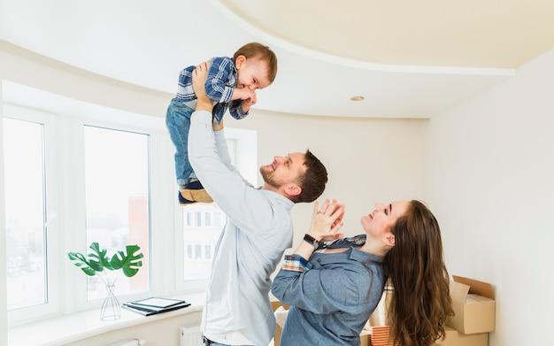 Een portret van een jong koppel spelen met een baby in een nieuw huis Gratis Foto