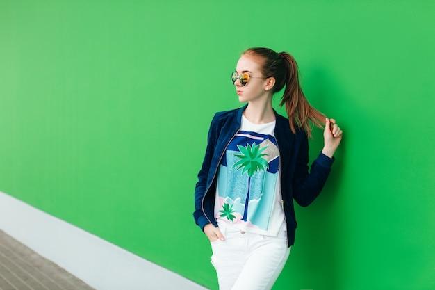 Een portret van een jong meisje buiten in de buurt van groene muur met witte lijn naar beneden. het meisje draagt een zonnebril, houdt haar staart in de hand en kijkt ver weg. Gratis Foto