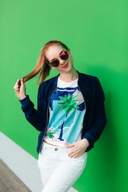 Een portret van een jong meisje in blauw jasje buiten dichtbij groene muur met witte lijn naar beneden. het meisje draagt een zonnebril, houdt haar staart in de hand en kijkt naar de camera. Gratis Foto