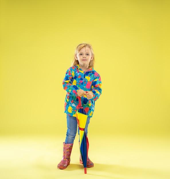 Een portret van volledige lengte van een helder modieus meisje in een regenjas met een paraplu van regenboogkleuren op een gele studiomuur Gratis Foto