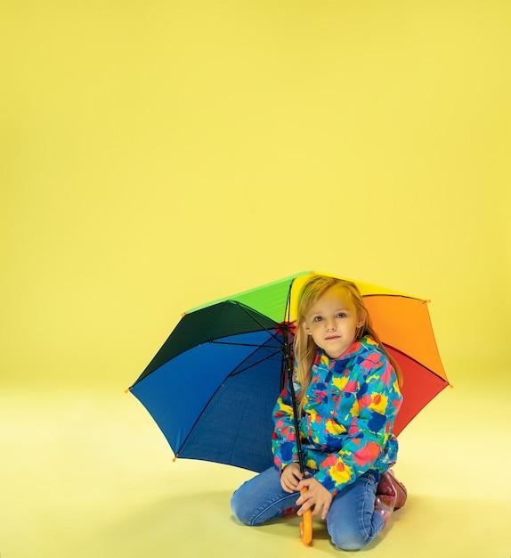 Een portret van volledige lengte van een helder modieus meisje in een regenjas Gratis Foto
