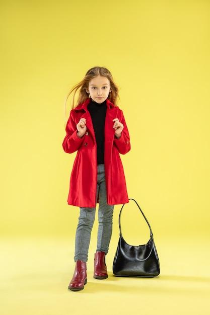 Een portret van volledige lengte van een helder modieus meisje in een rode regenjas met zwarte tas die zich voordeed op gele studiomuur Gratis Foto