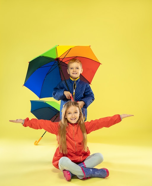 Een portret van volledige lengte van heldere modieuze kinderen in een regenjas Gratis Foto