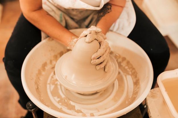 Een pottenbakker werkt aan het maken van een aarden pot op haar aardewerkwiel Gratis Foto