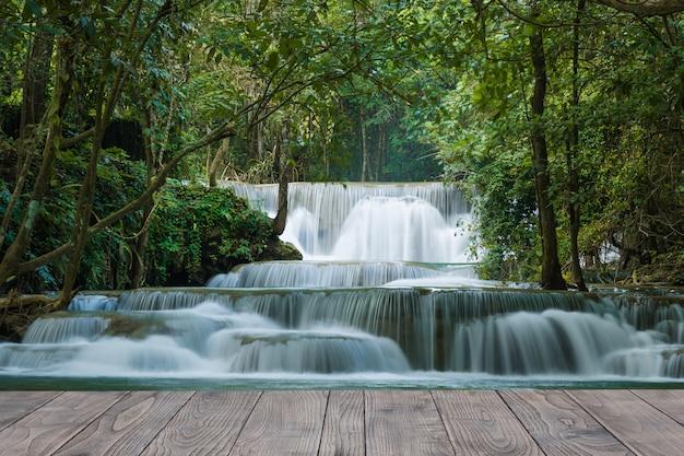 Een prachtige stroom van waterval in regenwoud met houten bureau Premium Foto