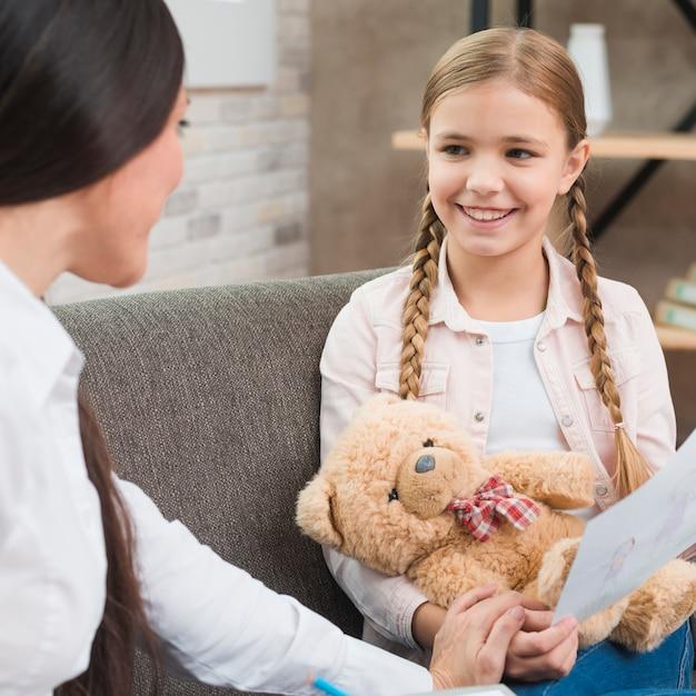 Een professionele psycholoog die een vergadering met een meisje heeft dat op bank zit Gratis Foto