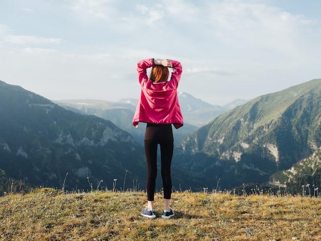 Een reiziger in legging, gympen en jasje rust in de bergen in de natuur. hoge kwaliteit foto Premium Foto