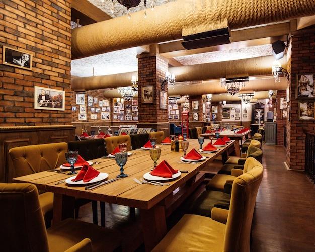 Een restaurant hal met rode bakstenen muren houten tafels en pijpen in het plafond Gratis Foto