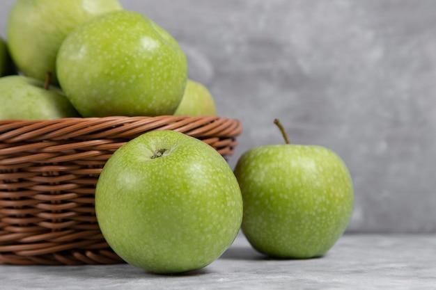 Een rieten mand met verse groene appels op steen Gratis Foto