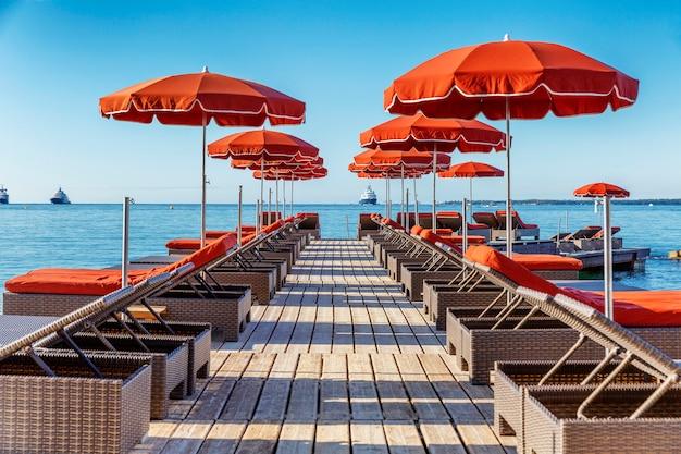 Een rij ligstoelen met oranje matrassen en parasols in een trendy resort. Premium Foto