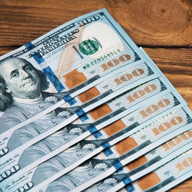 Een rij van contant geld honderd amerikaanse bankbiljetten op een houten achtergrond Premium Foto