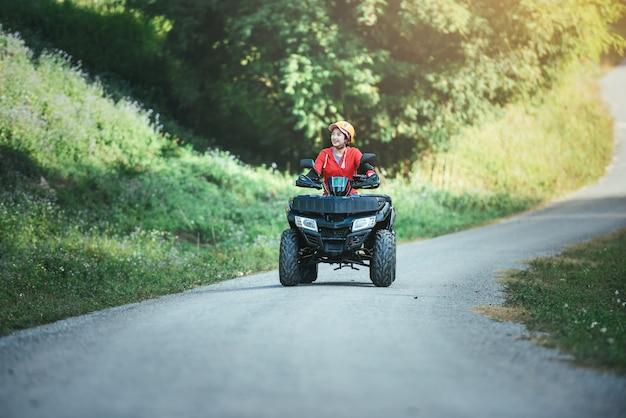 Een rit op de atv op de rode weg een rit op de atv op de weg. Premium Foto