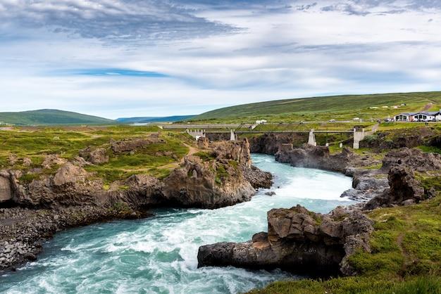 Een rivier van godafoss falls, akureyri, ijsland, omgeven door enorme rotsen en een betonnen brug Gratis Foto