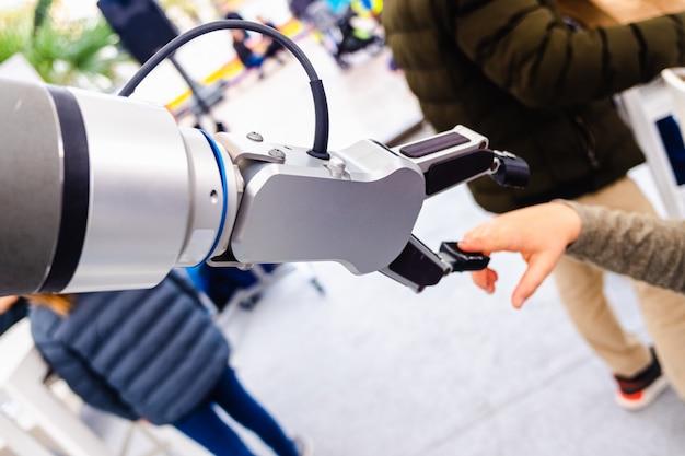 Een robotarm speelde met een kind in een innovatieve technische en industriële tentoonstelling. Premium Foto