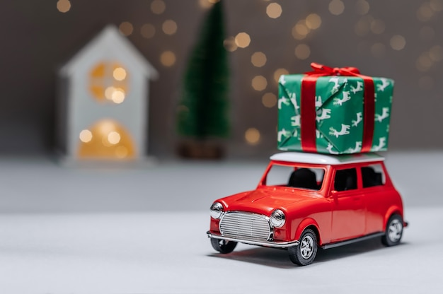 Een rode auto op de achtergrond van een bos en een huis brengt kerst-nieuwjaarscadeaus. Premium Foto