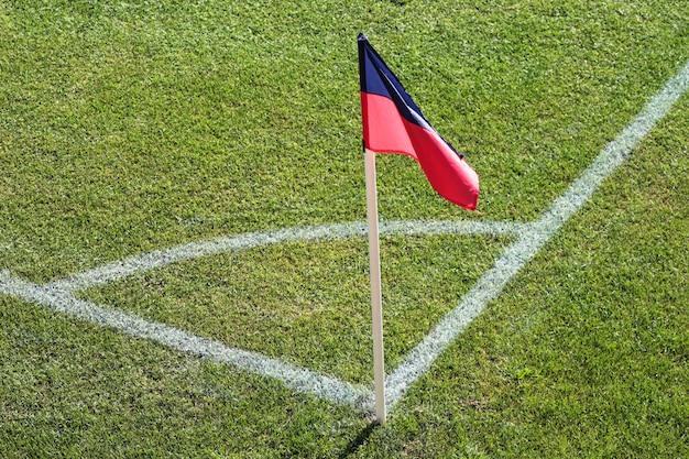 Een rode en blauwe vlag op één hoek van voetbalstadion en voetbalhoek van een voetbalveld Premium Foto
