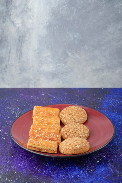 Een rode plaat met gezonde koekjes en heerlijke crackers op melkweglijst. Gratis Foto