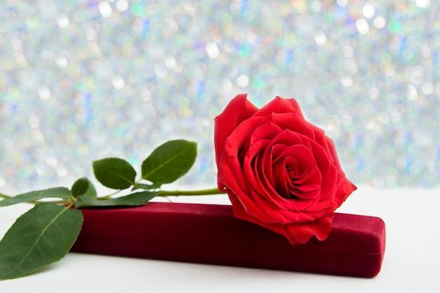 Een rode roos en sieraden aanwezig doos met boke achtergrond Premium Foto