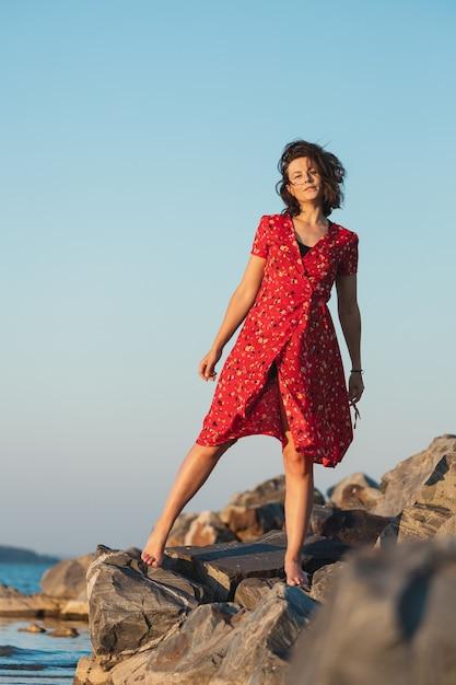 Een romantische wandeling van een vrouw met krullend haar in een rode jurk Premium Foto