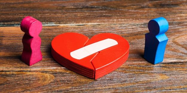 Een rood hart met een pleister en een paar in geliefden. Premium Foto
