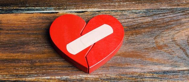 Een rood hart met een pleister. Premium Foto