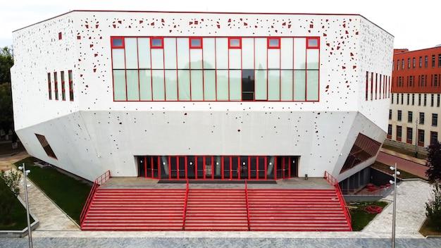 Een rood-wit gebouw met een modern uitzicht en trappen ervoor in boekarest, roemenië Gratis Foto