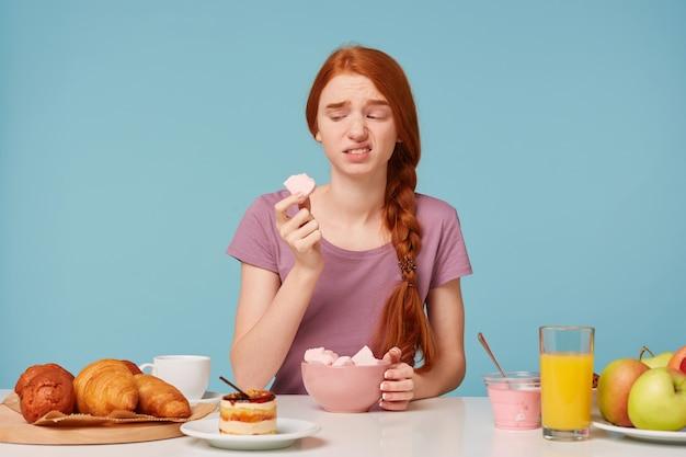 Een roodharig meisje dat tijdens het ontbijt aan een tafel zat, probeerde een marshmallow met fruit Gratis Foto