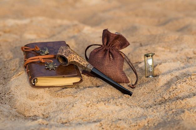 Een rookpijp, een zak tabak, een zandloper en een boek om in te voeren Premium Foto