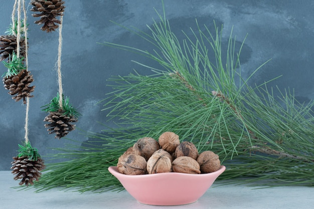 Een roze bord vol walnoten en kerst dennenappels op marmeren achtergrond. hoge kwaliteit foto Gratis Foto