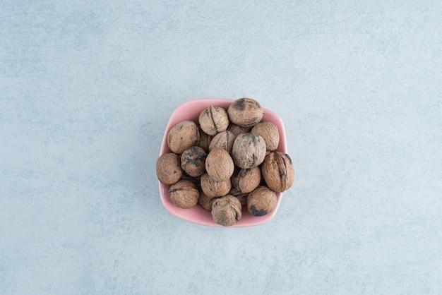 Een roze bordje vol noten op marmeren achtergrond. hoge kwaliteit foto Gratis Foto