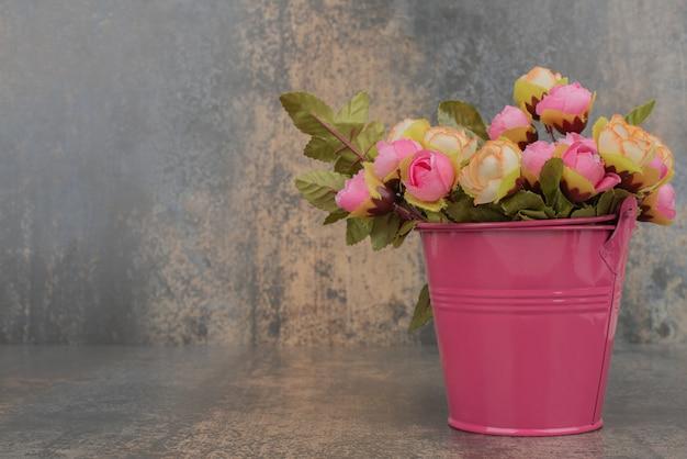 Een roze emmer met boeket bloemen op marmeren ondergrond. Gratis Foto