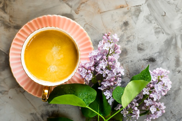 Een roze kop koffie met lila bloemen op een grijze betonnen tafel Premium Foto