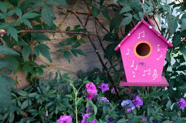 Een roze vogelhuis hangt op een boom die door petuniabloemen wordt omringd. Premium Foto