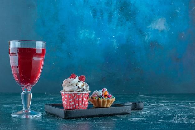 Een sapglas naast cupcakes op blauwe achtergrond. hoge kwaliteit foto Gratis Foto