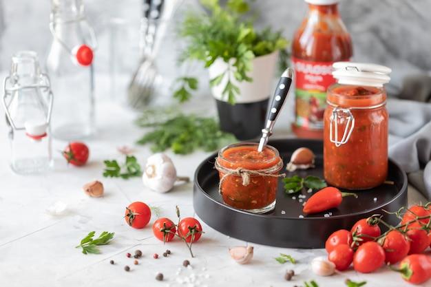Een saus van verse rode tomaten in een glazen pot op een zwarte plaat. takje verse kerstomaatjes, knoflook, hete peper, dille en peterselie op een witte tafel. een blikje zelfgemaakte ketchup Premium Foto