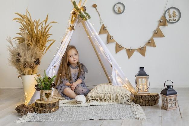 Een schattig klein meisje in een mooie jurk speelt thuis in een wigwam. nieuwjaar decoratie. Premium Foto